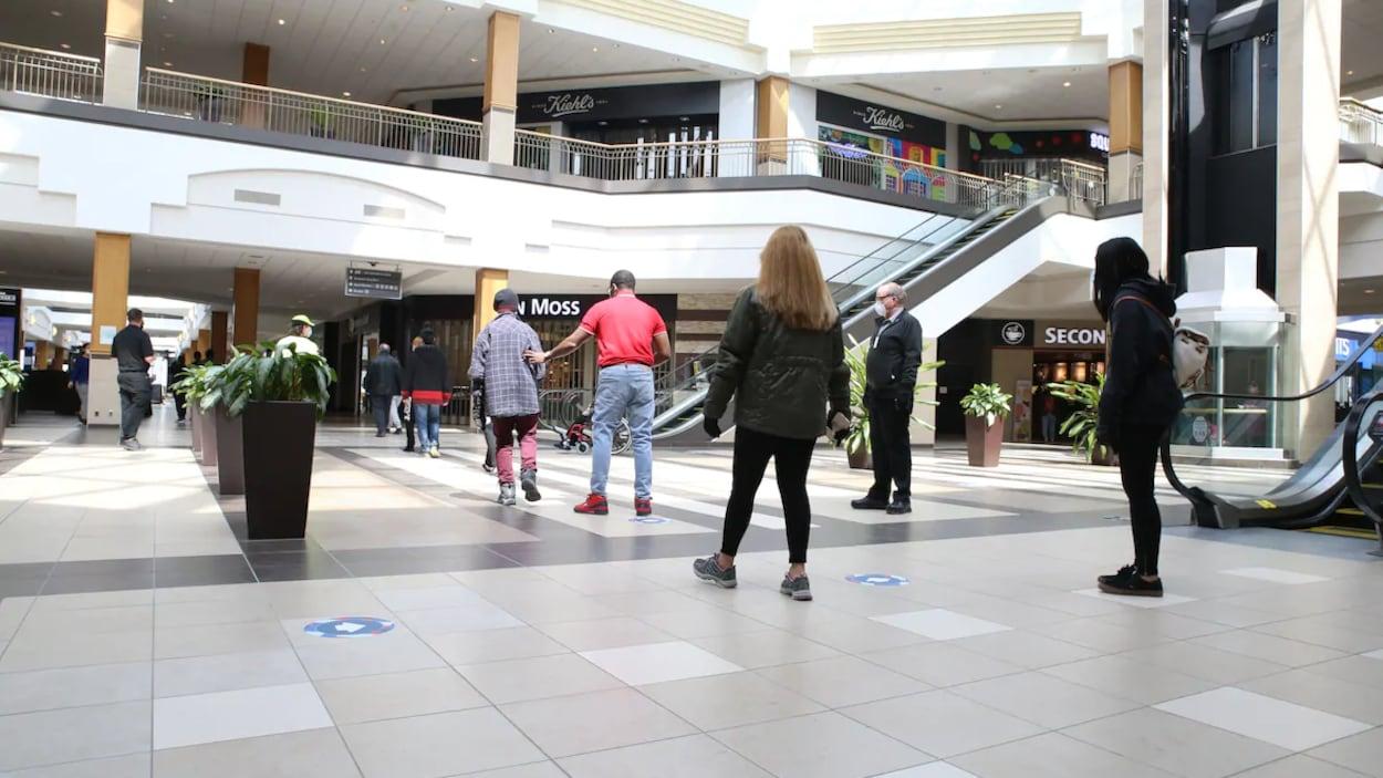 Des gens de dos debout dans un centre commercial. Un employé, qui porte un masque, les surveille pour s'assurer qu'ils respectent les règles de distanciation physique.