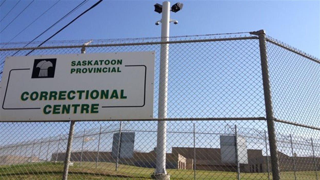 Pancarte du centre correctionnel de Saskatoon accrochée au grillage par un jour de beau temps.