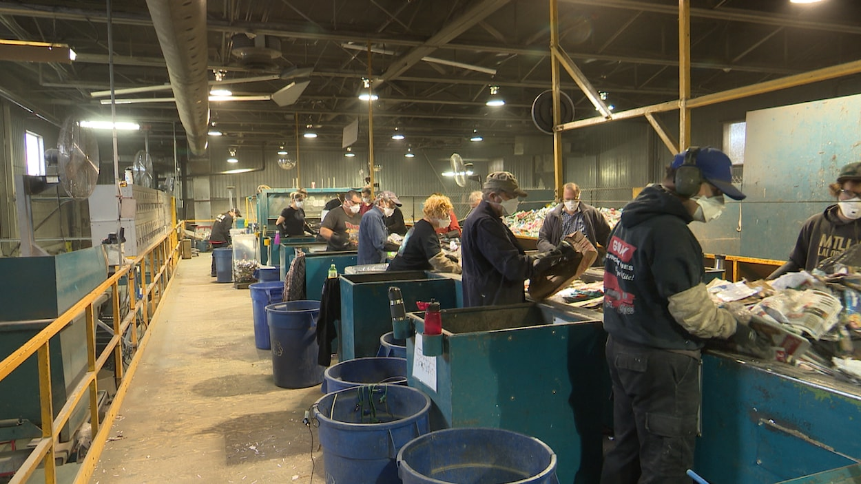 Des employés d'un centre de tri travaillent sur une chaine de travail pour faire le tri des différentes matières recyclables.