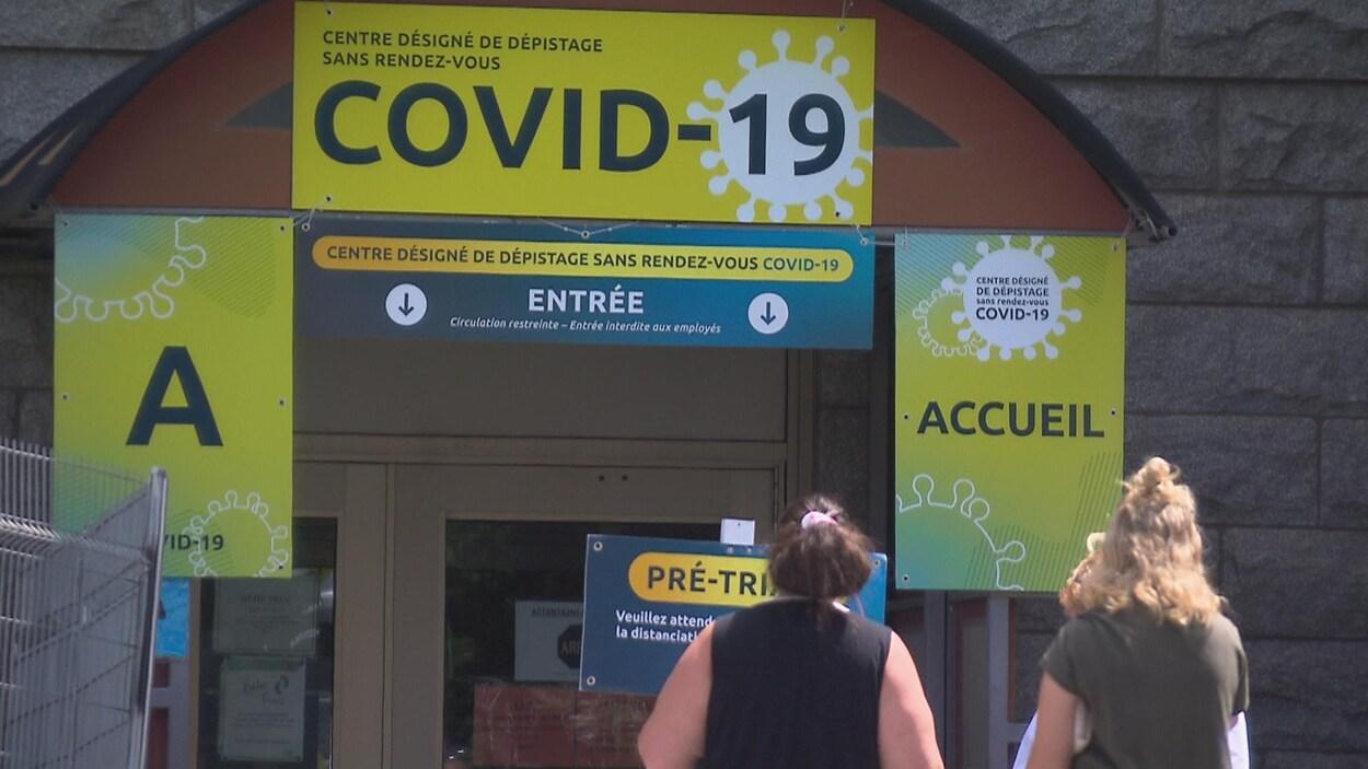 Deux personnes attendent à l'entrée du centre de dépistage sans rendez-vous de la COVID-19 de Sherbrooke.