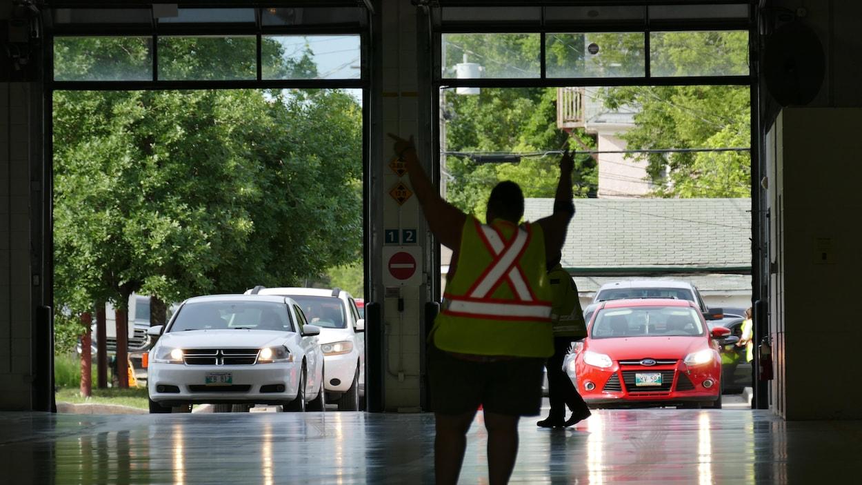 Des voitures font la queue pour entrer dans un centre de dépistage et un agent fait la circulation.