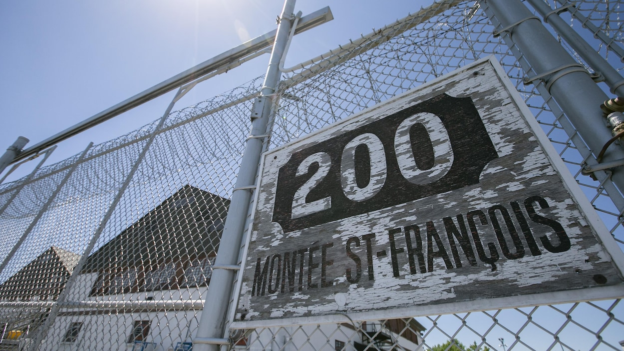 Une clôture à mailles de chaîne coiffée de barbelés, portant l'adresse « 200, montée Saint-François ».