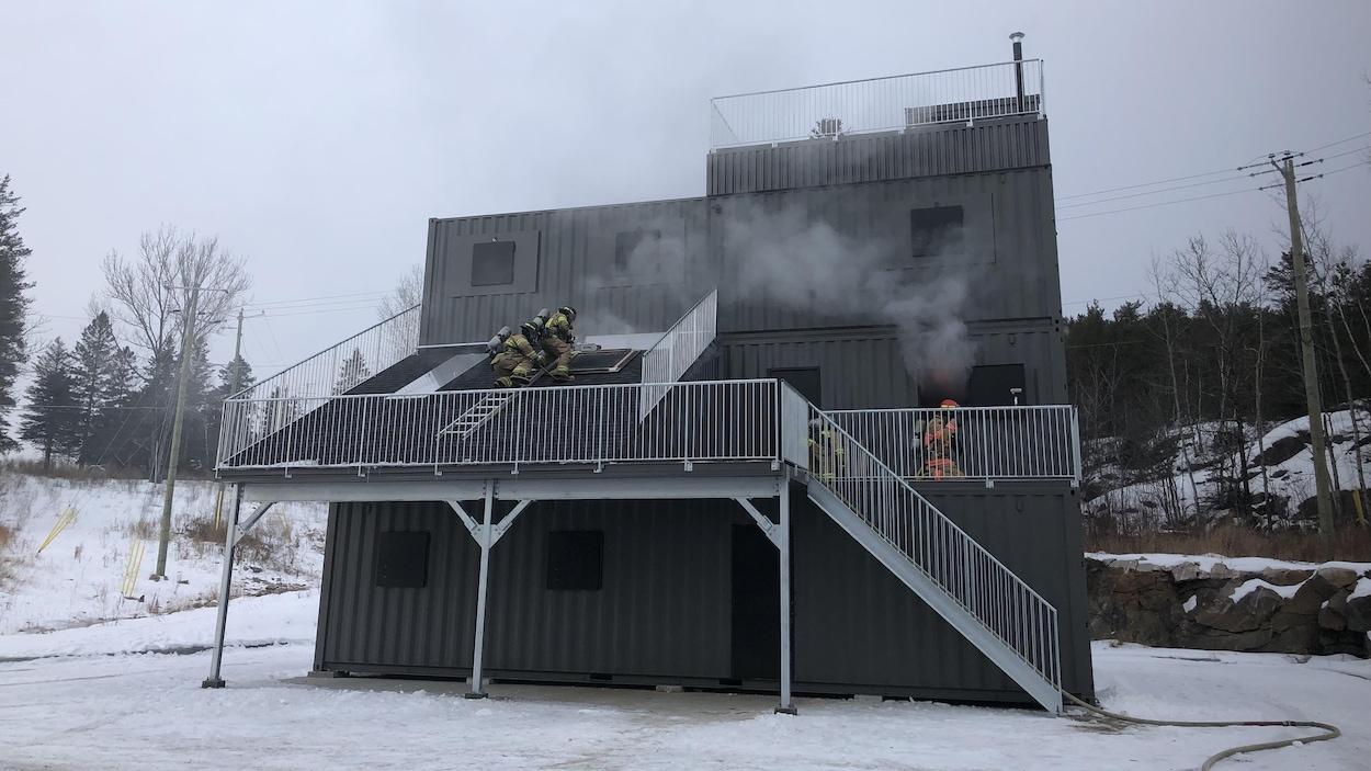 Un module d'entraînement fabriqué à partir de conteneurs maritimes autour duquel s'affairent des pompiers.