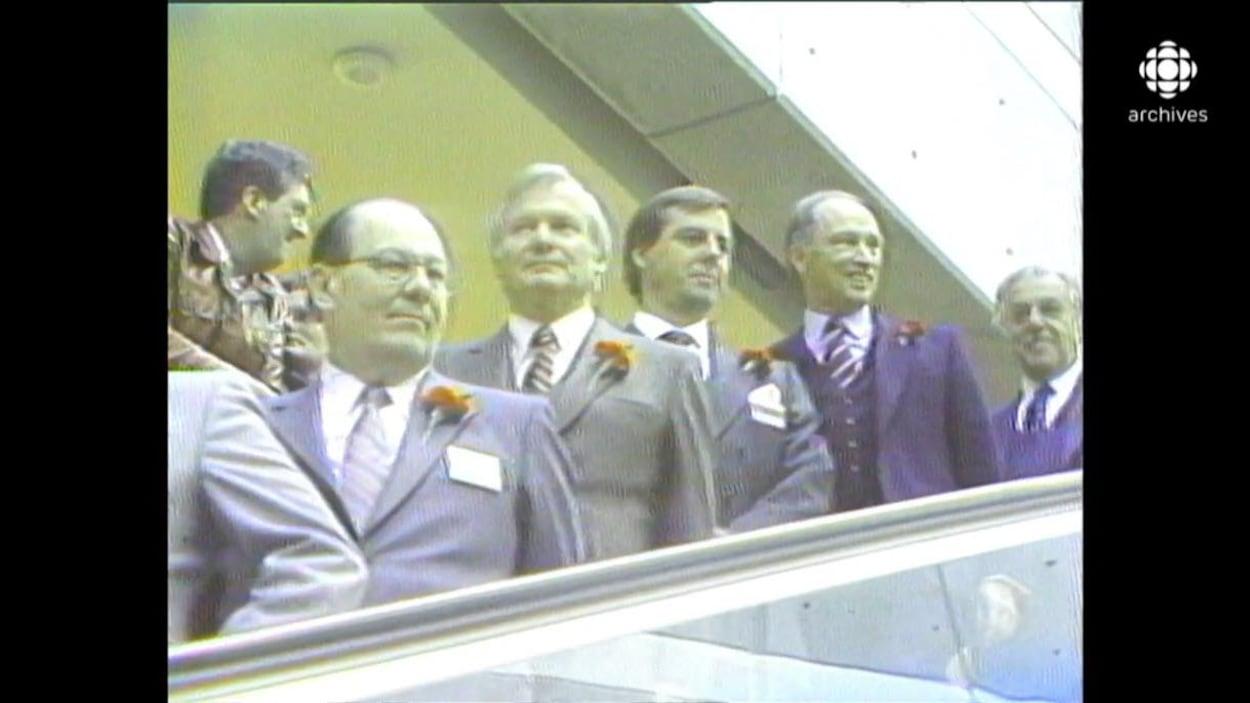 Dignitaires, dont Pierre Elliott Trudeau, en file dans l'escalier roulant du Centre Rideau lors de son inauguration.