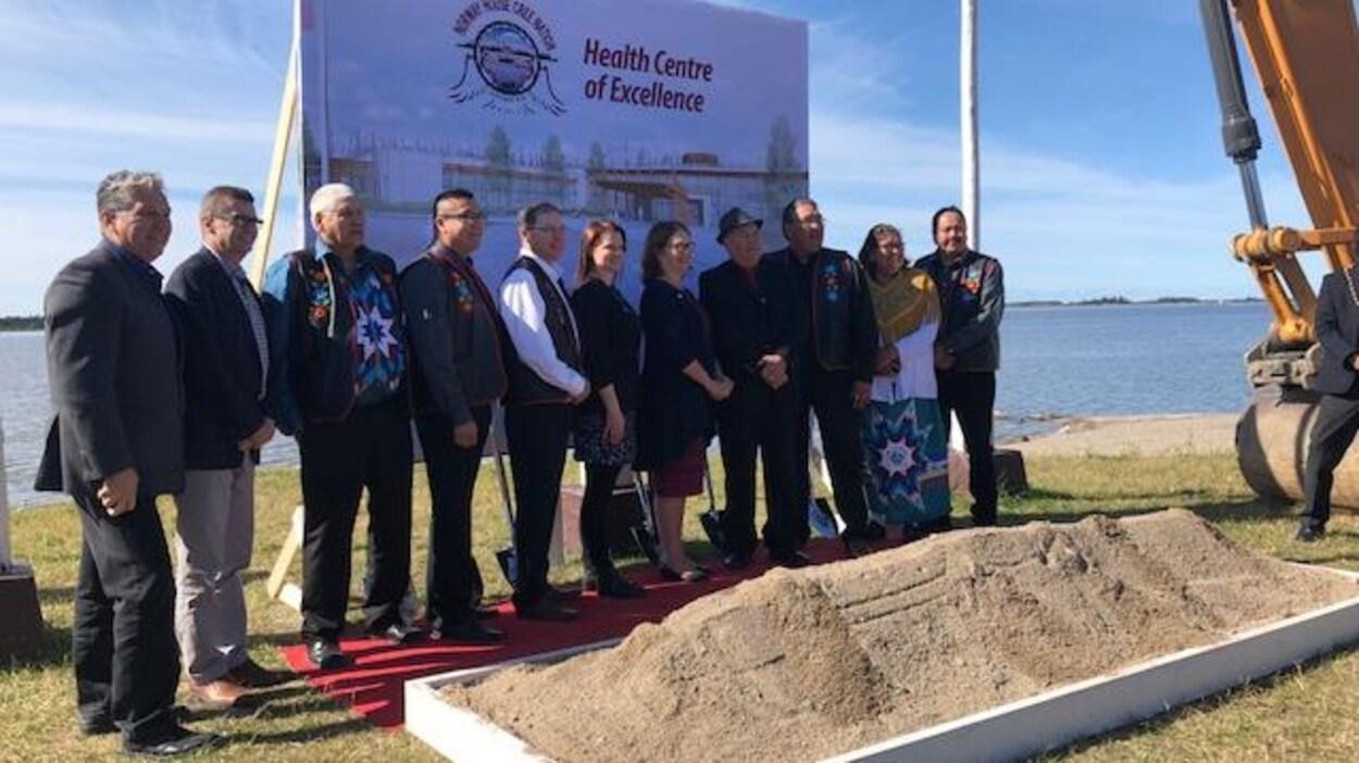 Plusieurs politiciens et leaders autochtones posent devant un bac de terre et près d'un grand panneau qui annonce le « centre d'excellence en santé de Norway House ».