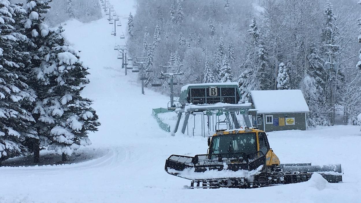 Une dameuse au pied d'une pente de ski du Mont-Édouard