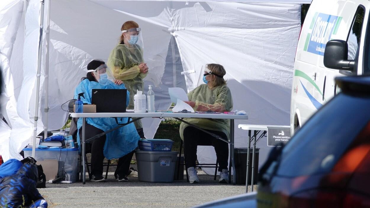 Trois travailleuses de la santé portant un équipement de protection autour d'une table placée devant un chapiteau, dans un stationnement.
