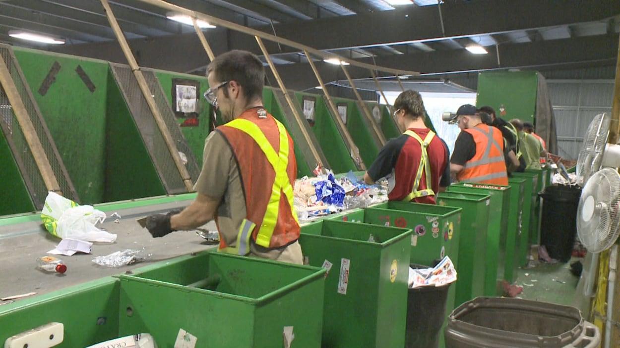 Des hommes travaillent sur une chaîne dans le centre de triage.