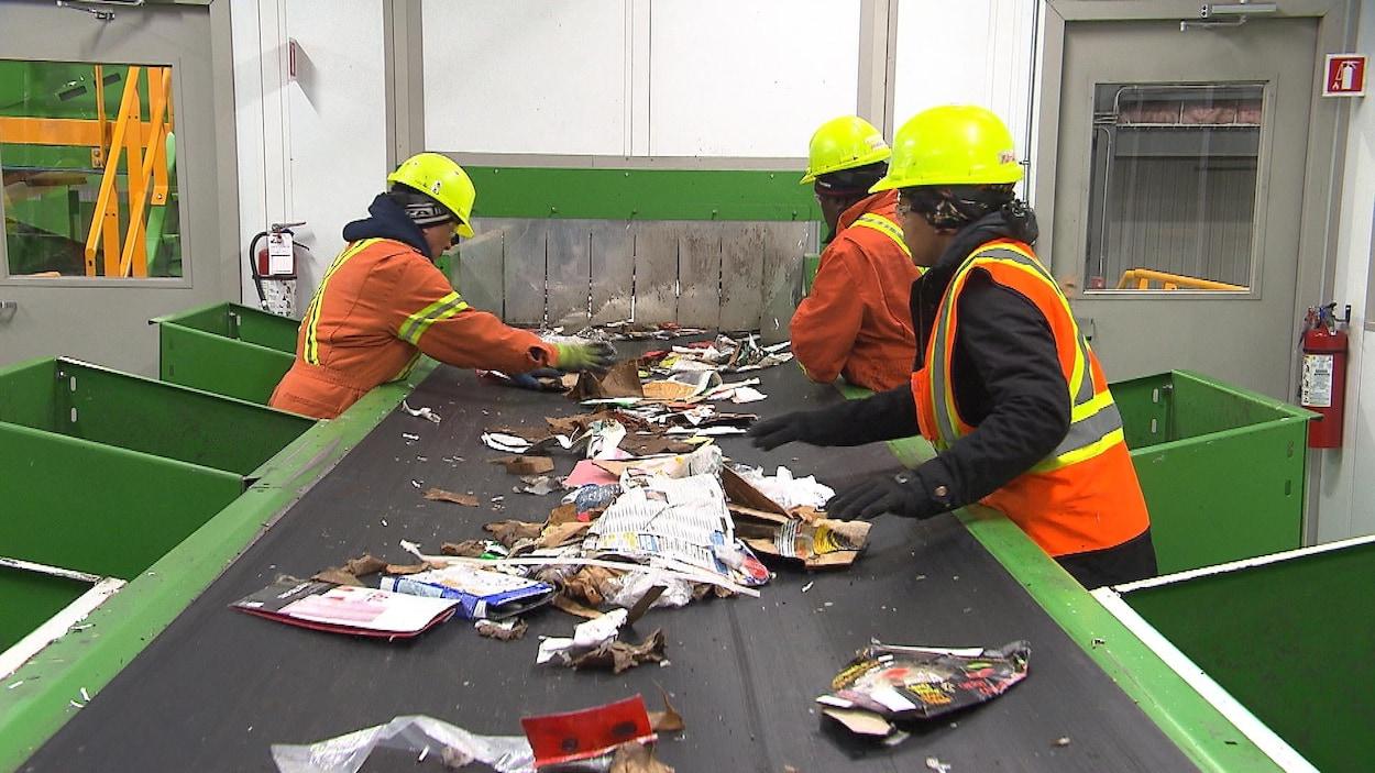 Des gens vêtus de casques et de dossards se tiennent autour d'un tapis roulant où défilent des matières recyclables à trier.