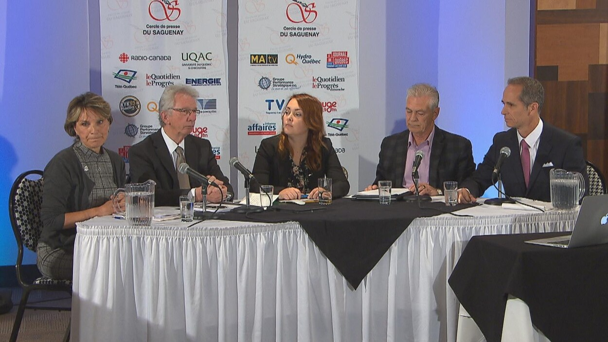 La présidente du Cercle de presse et les quatre candidats assis à une même table.