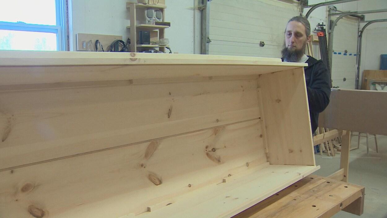 Un homme barbu tenant entre ses mains un cercueil en bois.