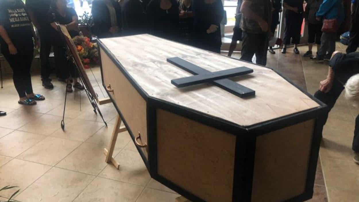 Un cercueil entouré de manifestants.
