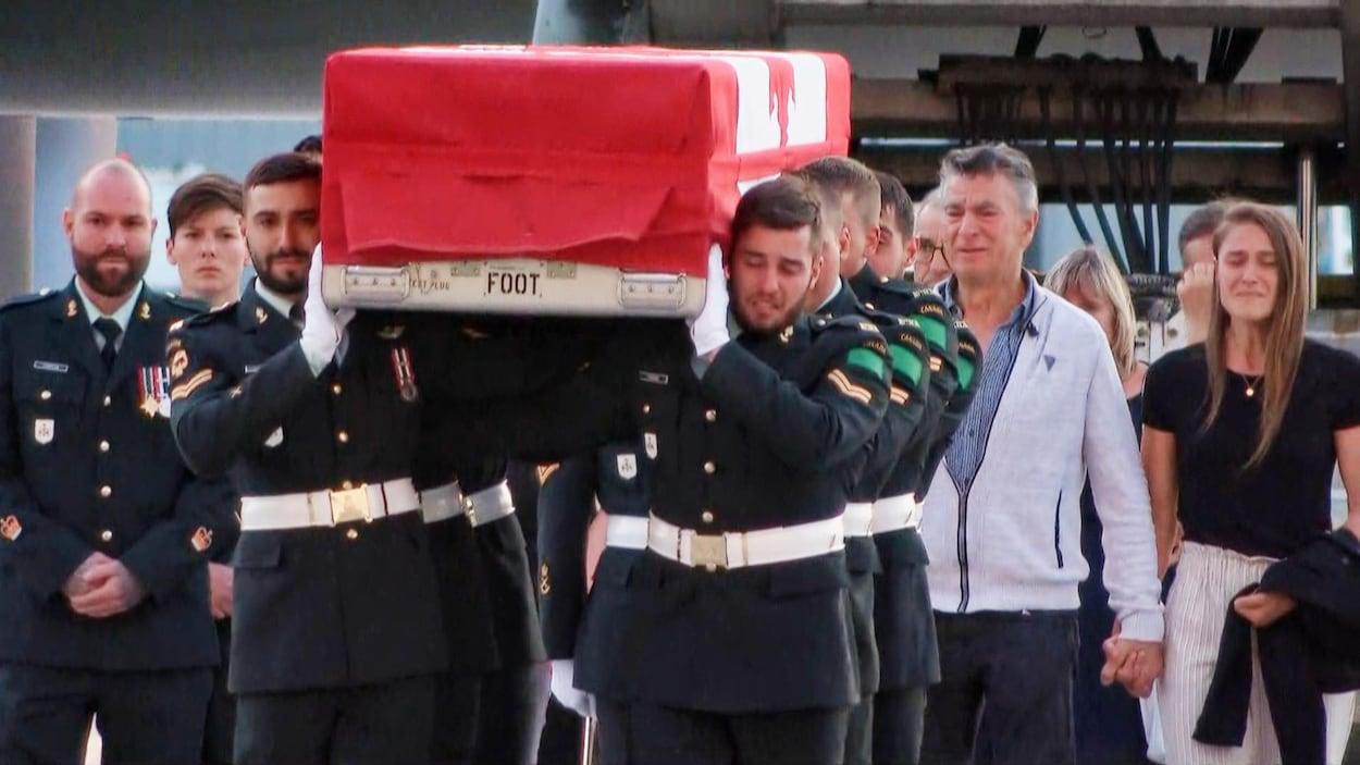 Des soldats en pleurs portent le cercueil de Patrick Labrie, recouvert d'un drapeau canadien.
