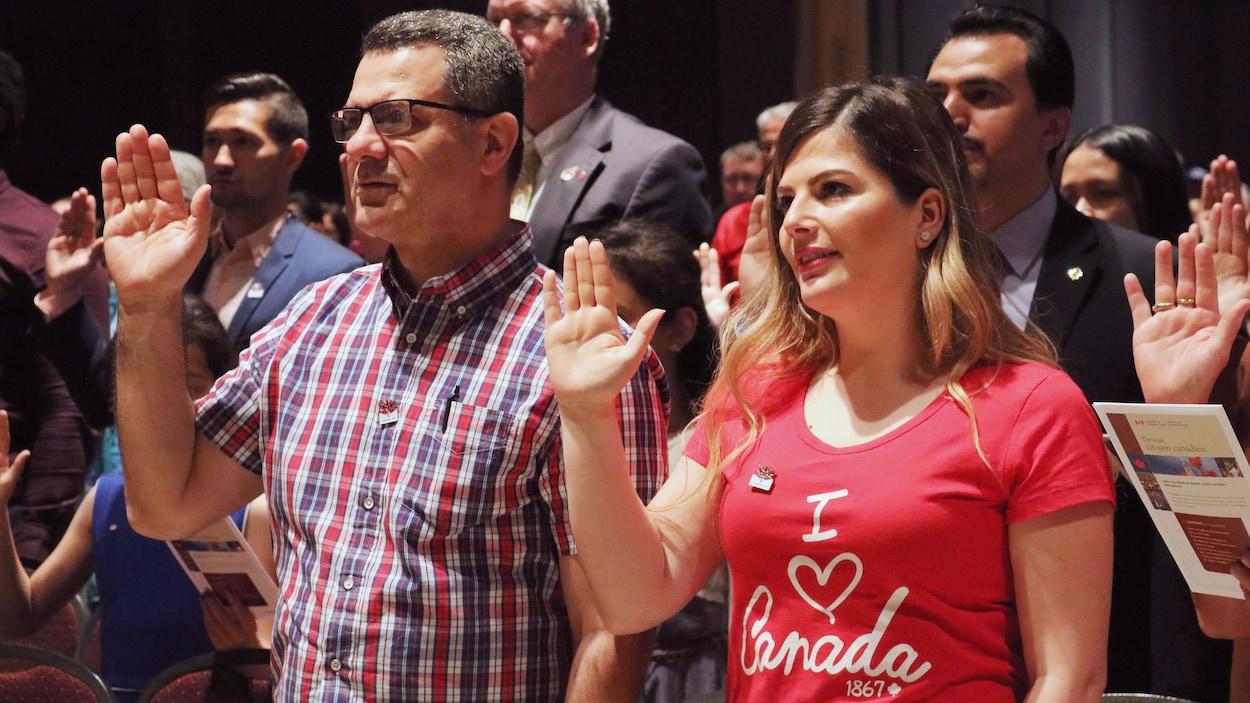 Hommes et femmes la main droite levée lors d'une cérémonie de citoyenneté canadienne.