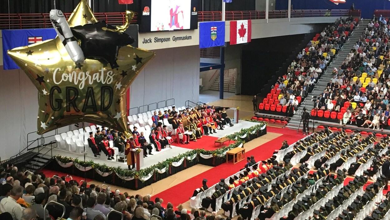 """Un ballon indiquant en anglais """"félicitations diplômés"""" flotte dans les airs dans une salle où se déroule une cérémonie de remise de diplômes."""