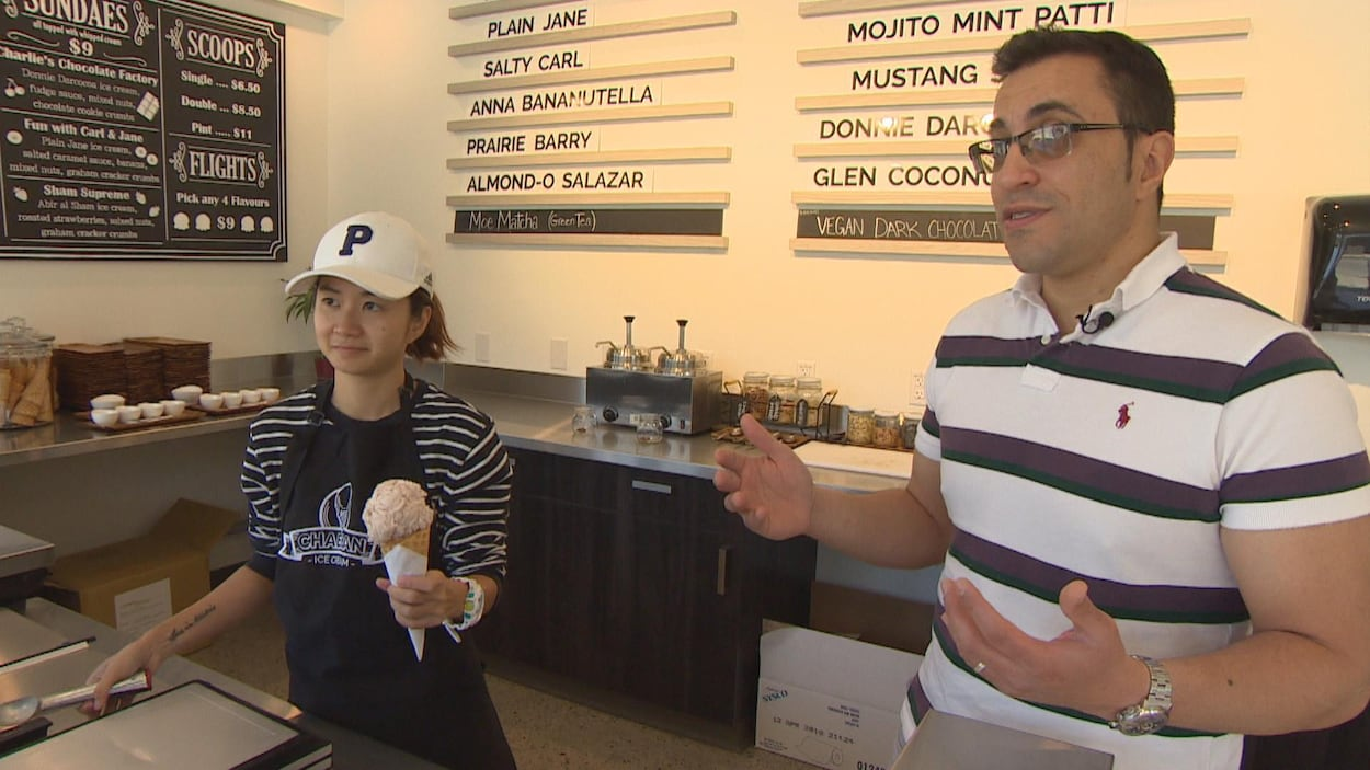 Une homme et une femme dans une boutique, la femme tient un cornet de crème glacée.