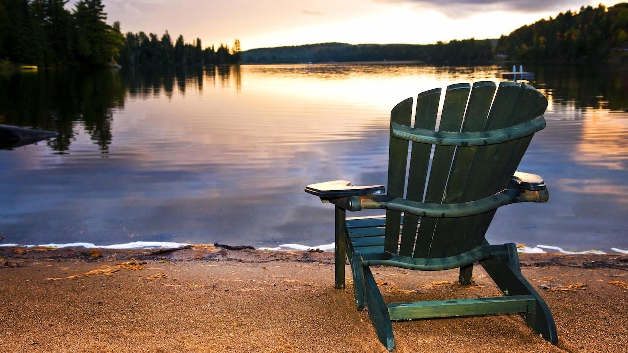Une chaise installée sur le bord d'un lac au coucher de soleil.