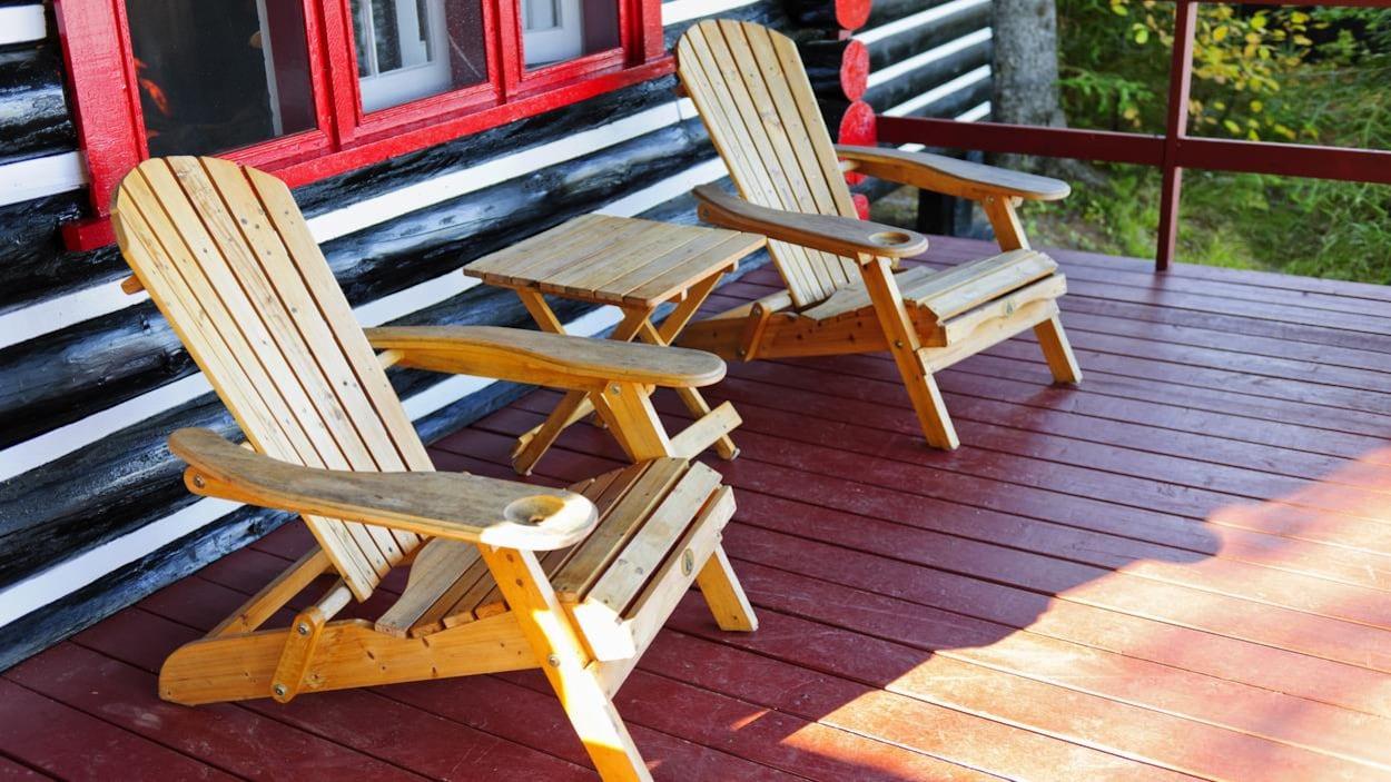 Deux fauteuils adirondack sur la terrasse d'un chalet en bois.