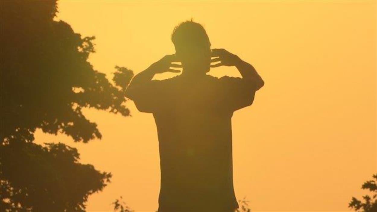 Un homme debout face au soleil.