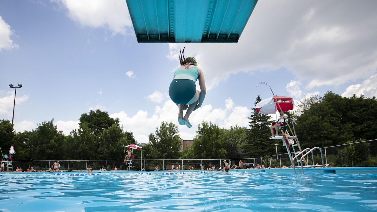 Une enfant saute dans une piscine publique.