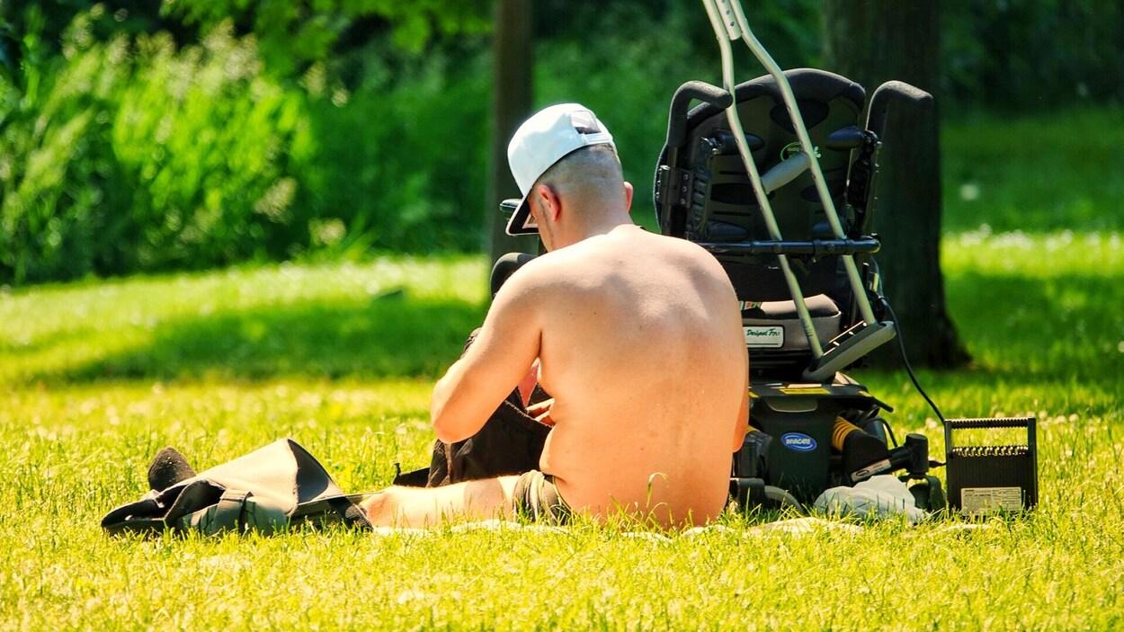 Un homme est assis dans l'herbe au soleil près d'un fauteuil roulant.