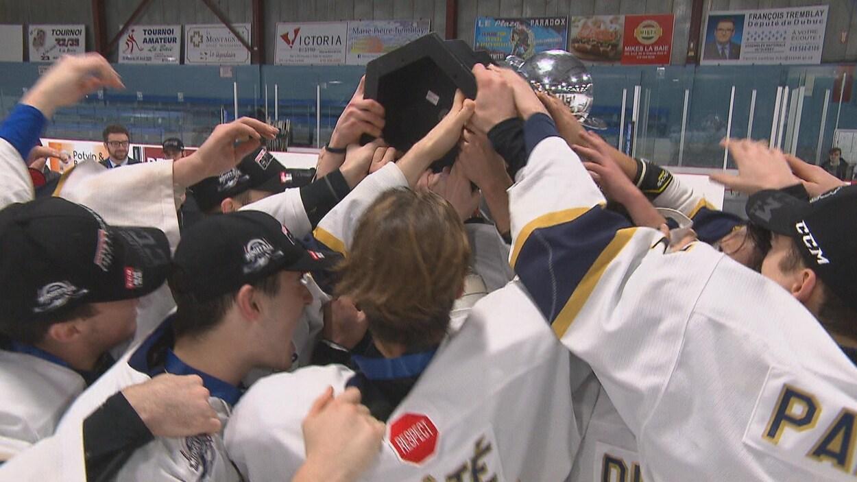 Des joueurs de hockey se massent autour d'un trophée.