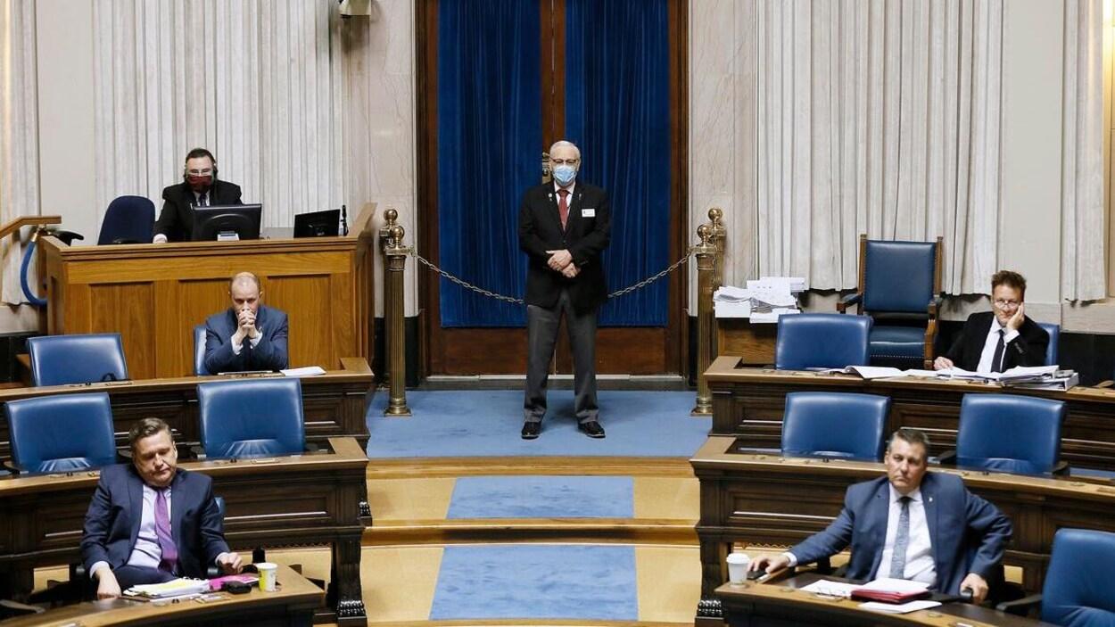 Six hommes dans la Chambre de l'Assemblée législative, dont deux avec des masques, tous à deux mètres les uns des autres.