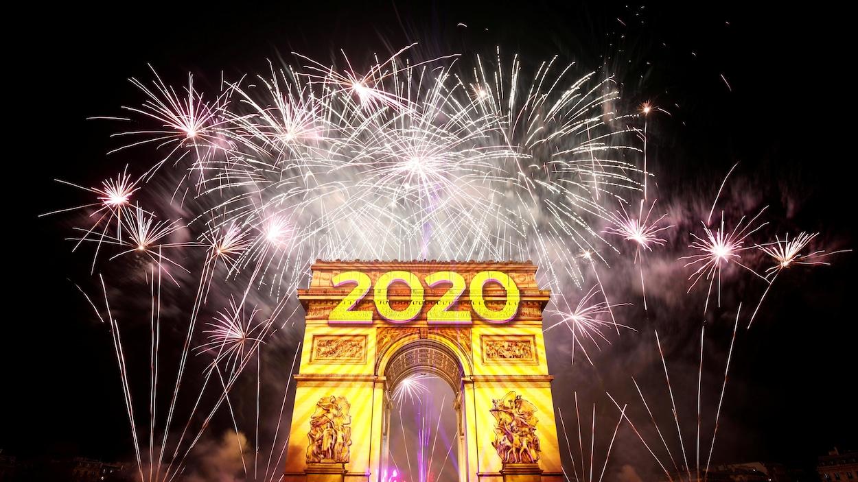 Le feu d'artifice illumine le ciel au dessus de l'Arc de Triomphe.