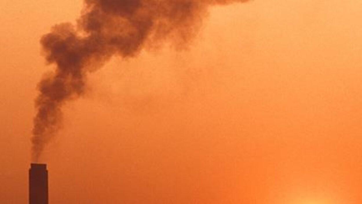 Une cheminée émet de la fumée sur fond de ciel orange.