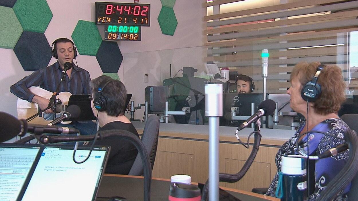 Un chanteur dans un studio de radio devant deux femmes qui l'écoutent