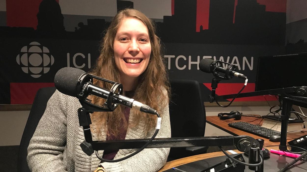 Une femme sourit devant un micro de radio.