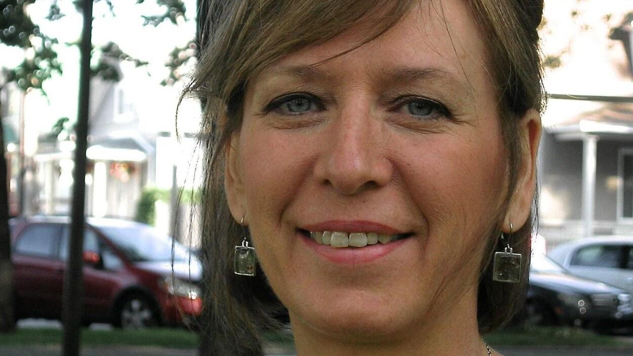 Portrait en couleur de l'autrice Chantal Fortier, en extérieur. Elle porte des boucles d'oreilles et un collier. On aperçoit en arrière-plan des arbres, des maisons et des voitures stationnées.