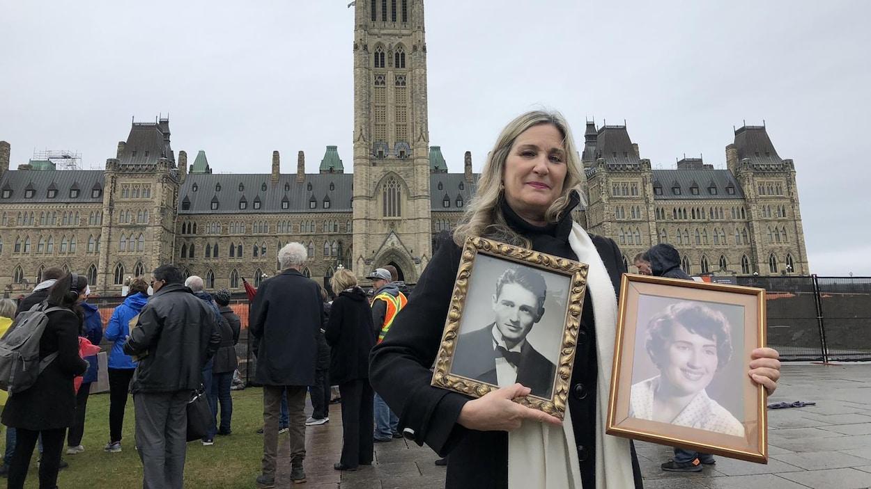 Chantal Jacob devant le Parlement à Ottawa avec des photos encadrées de ses parents.