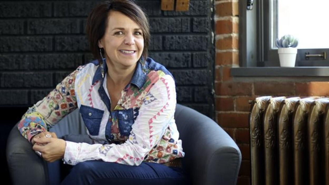 Une femme vêtue d'une chemise à motifs multicolores est assise les mains jointes dans un fauteuil bleu.