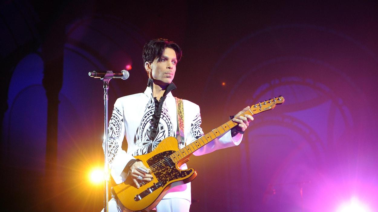 Le chanteur Prince joue de la guitare sur scène devant un microphone lors d'un concert à Paris, en 2009.