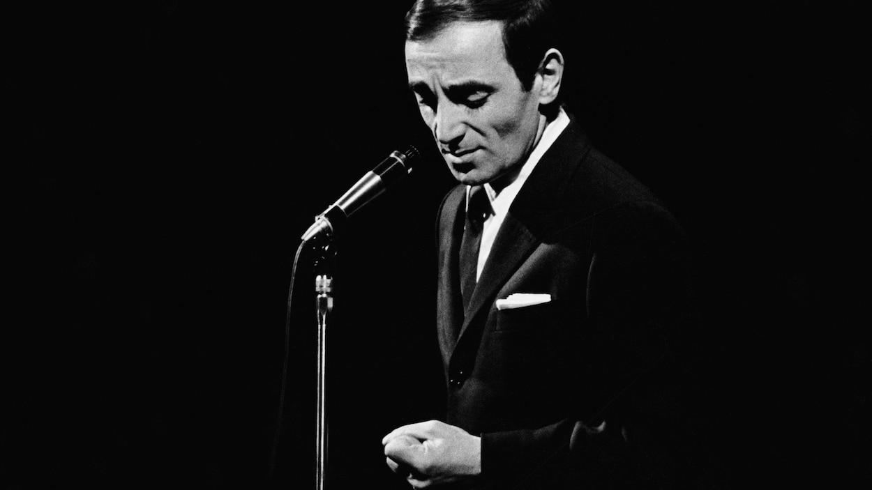 Dans une salle de spectacles, debout sur une scène, le chanteur français Charles Aznavour chante, le poing fermé.