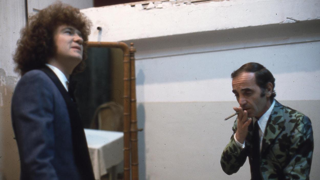 Robert Charlebois regarde en l'air et Charles Aznavour fume une cigarette.