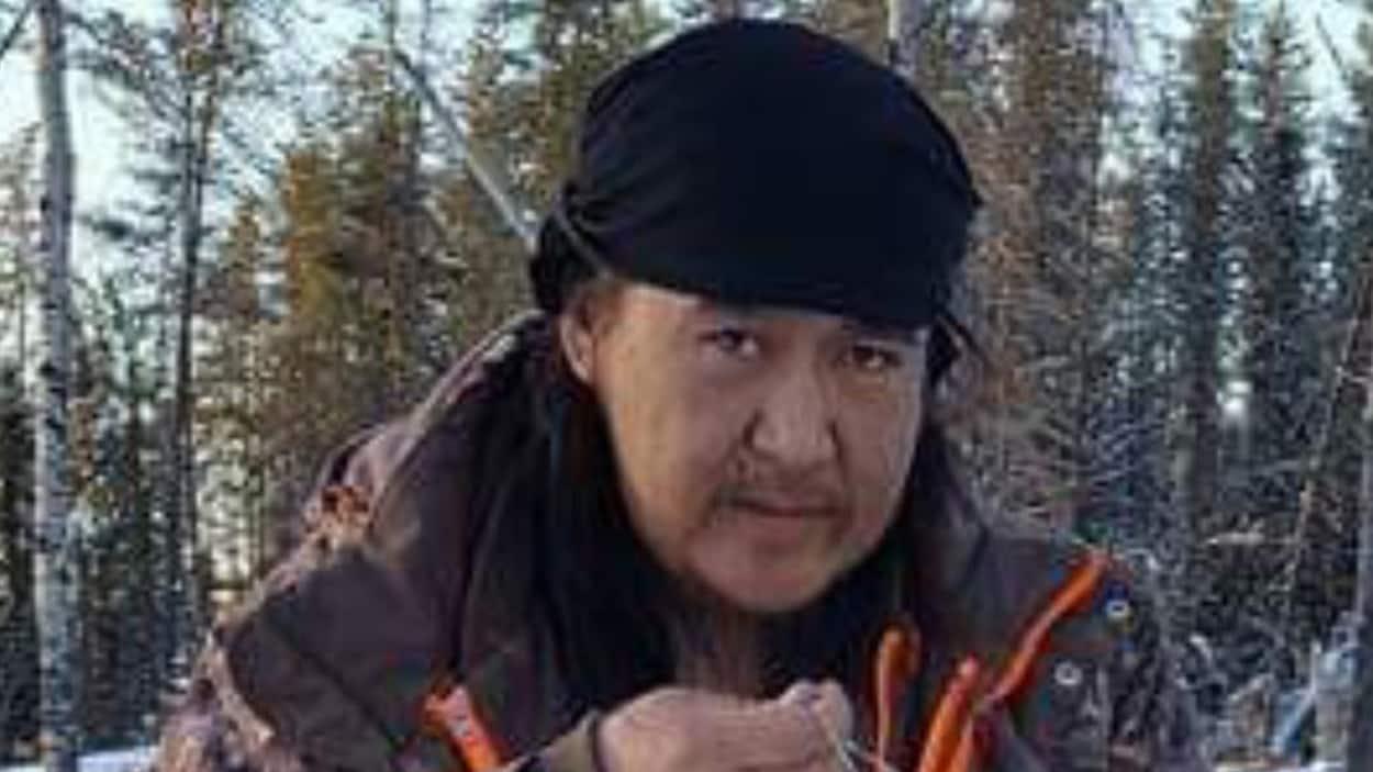 Un Autochtone regarde la caméra pendant qu'il travaille avec un fil dans les mains.