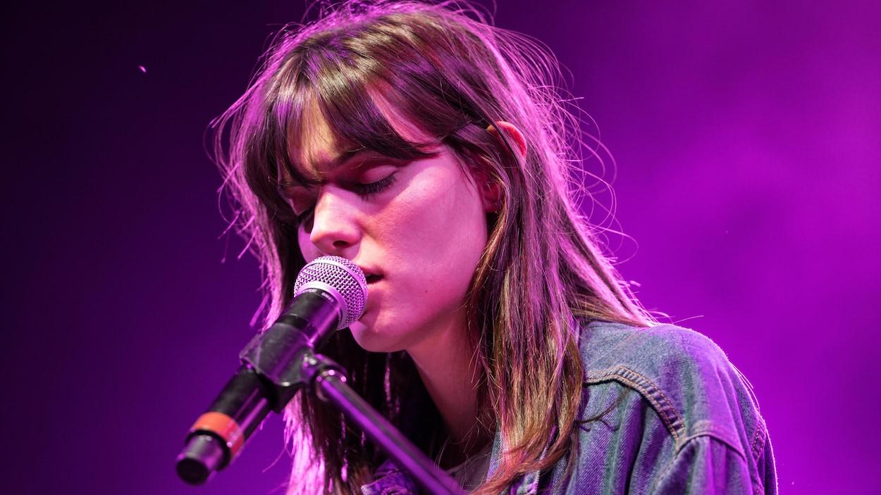 La chanteuse Charlotte Cardin chante les yeux fermés avec un micro très près de sa bouche.