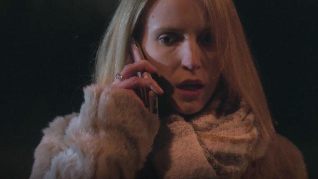 La jeune femme blonde parle au téléphone.