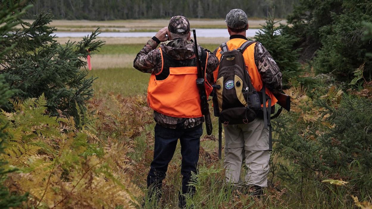 Deux chasseurs à l'orée d'un bois observe une étendue ouverte.