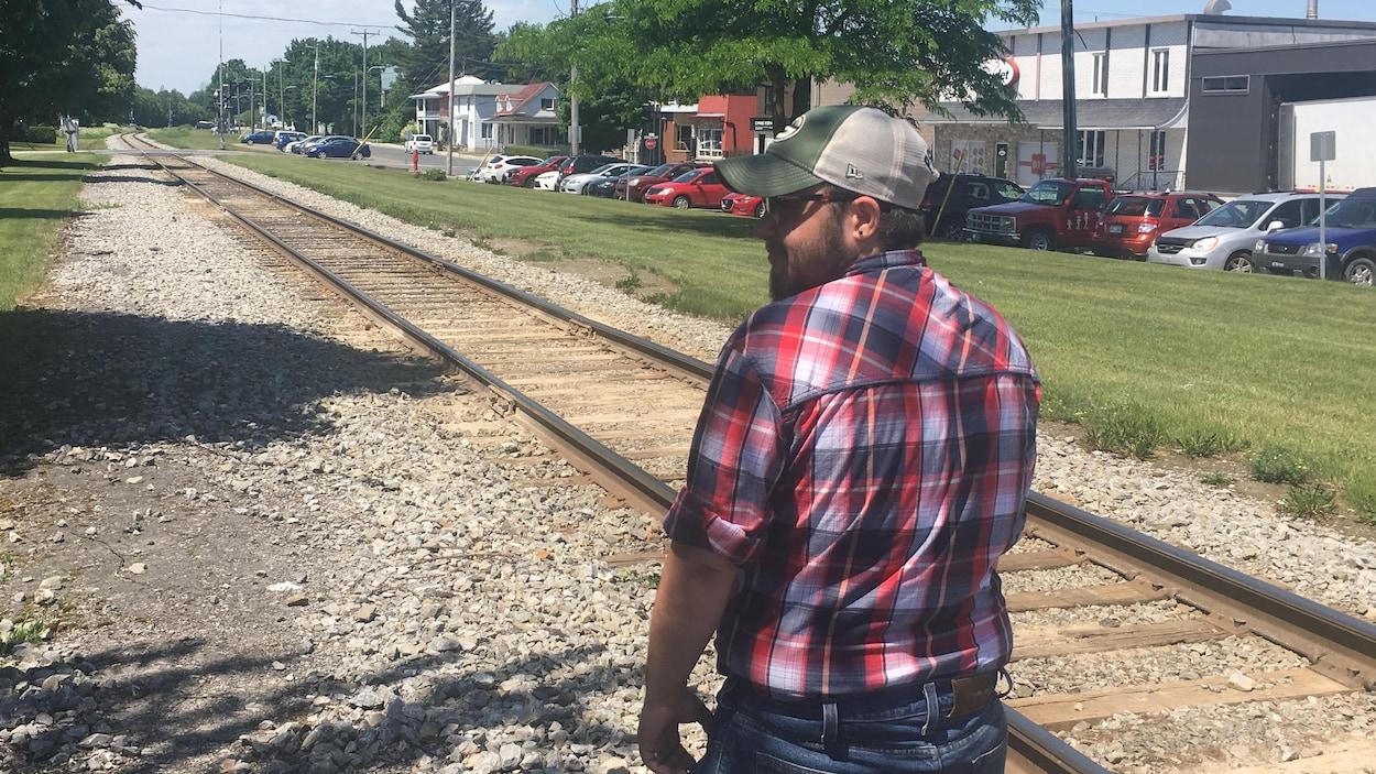 Un homme marche le long d'une voie ferrée.