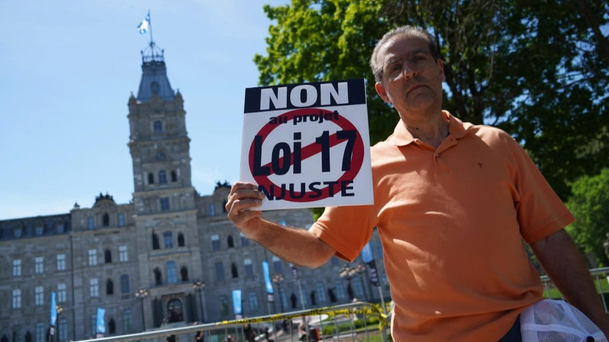 Un homme portant une pancarte en arrière plan l'Assemblée nationale.