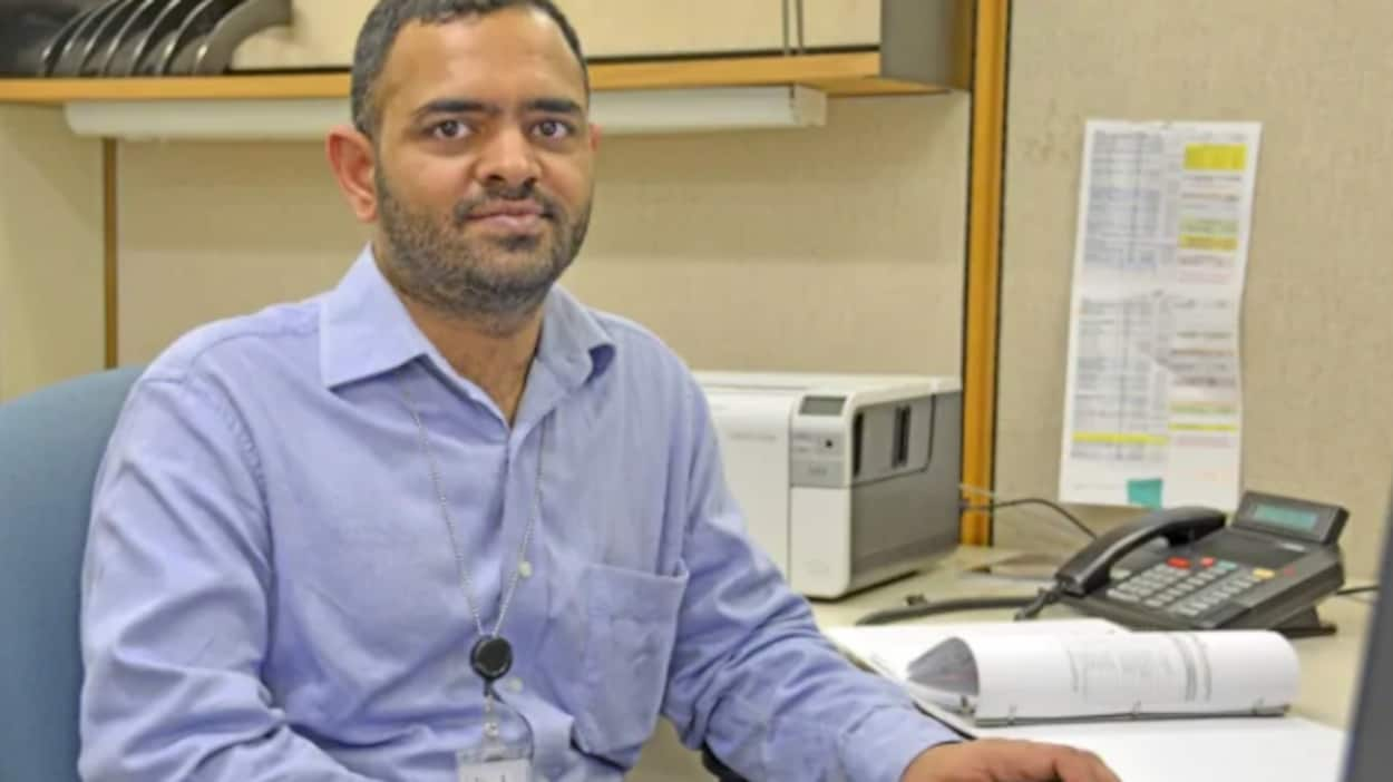 Iqbal Singh Sharma est assi devant son ordinateur avec une souris à la main