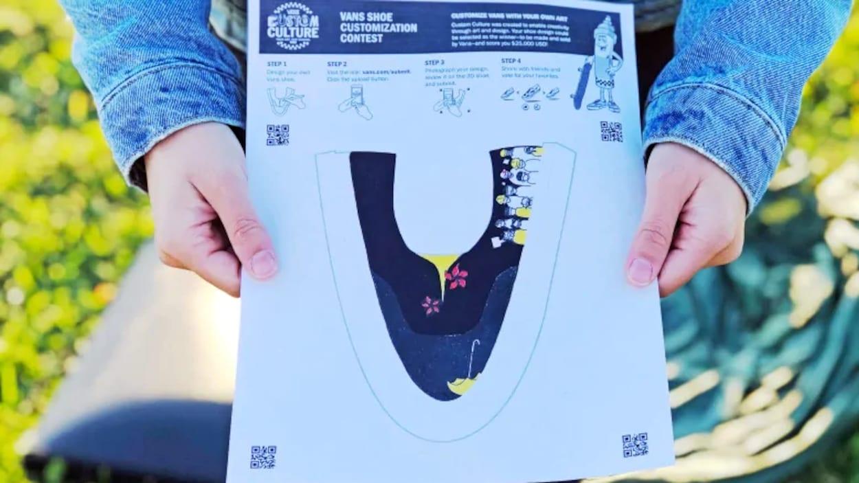 Une jeune fille présente le croquis d'une chaussure ornée de dessins.