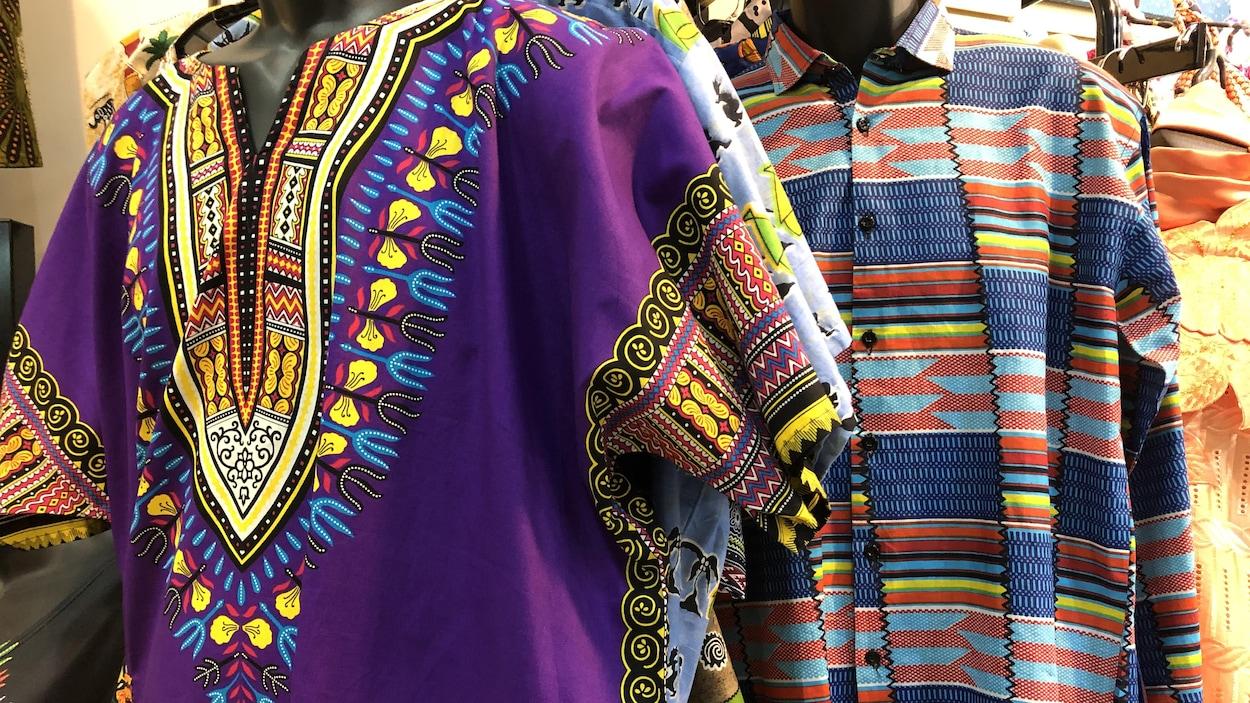 Plusieurs vêtements colorés sur des mannequins dans un magasin.