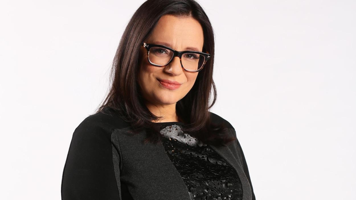 Portrait en couleur de l'autrice autochtone Cherie Dimaline, sur fond blanc. Elle a les cheveux lâchés, porte des lunettes, un chandail noir à manches trois-quarts, et a des tatouages sur les avant-bras.