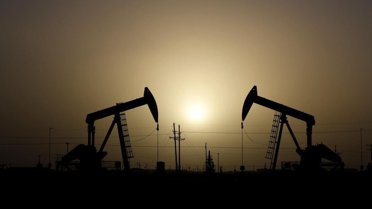Des chevalets de pompage d'une entreprise pétrolière sont en activité, au coucher du soleil.
