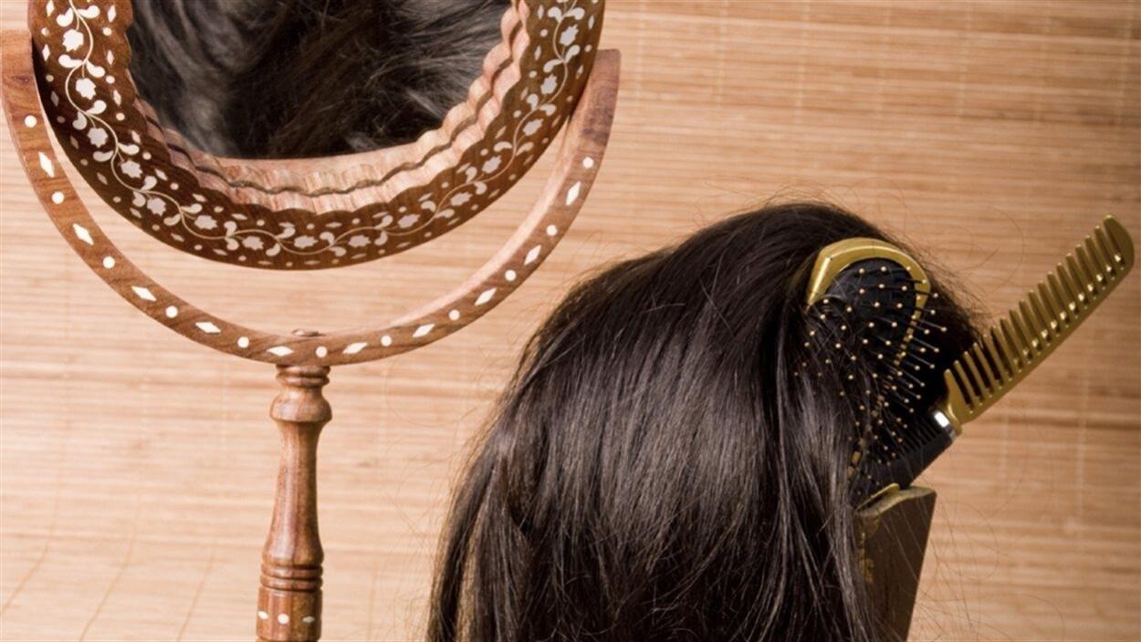 Une perruque de cheveux bruns repose aux côtés de brosses et d'un miroir.