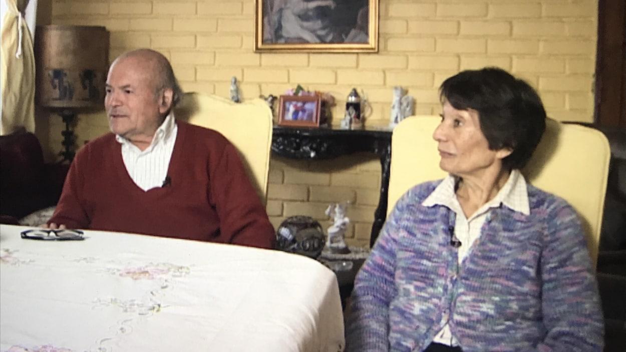 Un homme et une femme âgés répondent aux questions d'un journaliste.